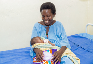 A happy mother smiling at her new born at Kirehe Hospital, Rwanda (Photo: Andre Rugema, RBC, 2019)