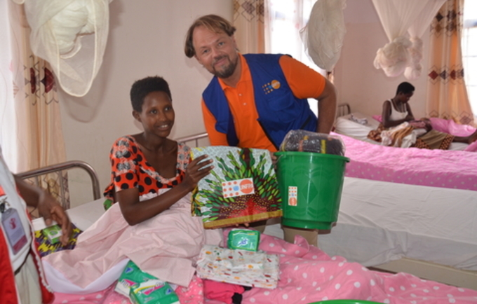 A refugee new mother receives a dignity kit after a few hours of birth from Mr. Mark Bryan Schreiner, UNFPA Rep.